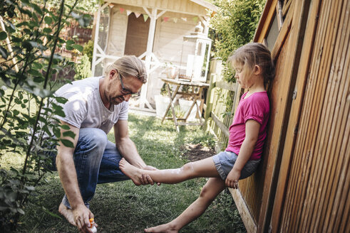Father applying sunscreen on daughter's legs in garden - JOSF00586