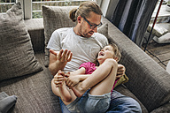 Father playing with daughter on sofa - JOSF00589