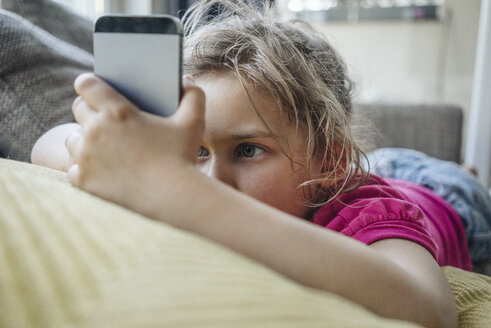 Girl lying on couch using smartphone - JOSF00592