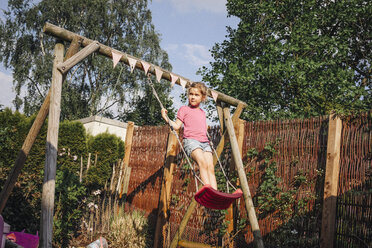 Girl standing on swing in garden - JOSF00595