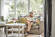 Man relaxing on couch using cell phone - JOSF00598