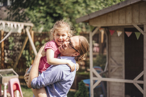 Father carrying daughter in garden - JOSF00607