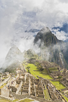 Peru, Andes, Urubamba Valley, clouds and fog above Machu Picchu with mountain Huayna Picchu - FOF08839