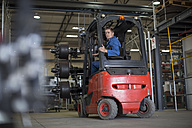 Factory working driving a fork lift in warehouse - ZEF12760