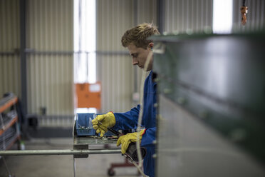 Factory worker in truck manufacture assembling truck parts - ZEF12763