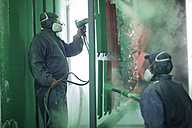 Painters spraying steel components in spray booth of a factory - ZEF12778