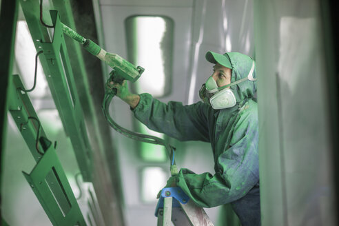 Painters spraying steel components in spray booth of a factory - ZEF12781