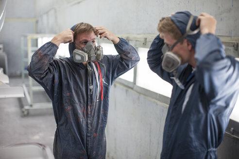 Factory worker in truck manufacture adjusting respirators - ZEF12790