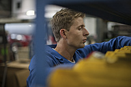 Factory worker in truck manufacture searching for tools - ZEF12793
