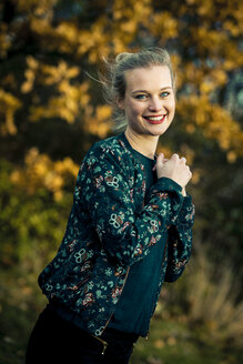 Portrait of smiling young woman in autumnal forest - NGF00388