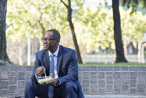 Businessman sitting on outdoor stairs having lunch - WESTF22581