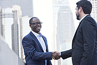 Two businessmen shaking hands in the city - WESTF22584