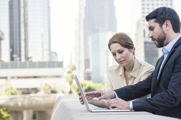 Businessman and businesswoman using laptop together - WESTF22587