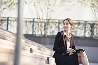 Businesswoman sitting on stairs with tablet and takeaway coffee - WESTF22590