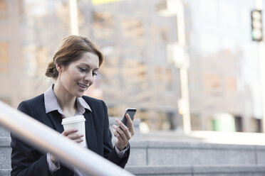 Smiling businesswoman holding cell phone and takeaway coffee - WESTF22593