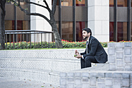 Businessman sitting on outdoor stairs having lunch - WESTF22602
