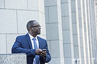 Businessman holding cell phone outdoors looking around - WESTF22614