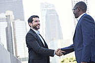 Two businessmen shaking hands in the city - WESTF22638