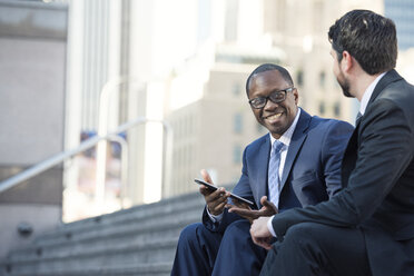 Smiling businessmen sitting on stairs sharing tablet with colleague - WESTF22644