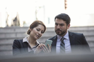 Businesswoman sharing cell phone with colleague - WESTF22647