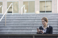 Businesswoman checking cell phone outdoors - WESTF22650