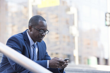 Businessman checking cell phone outdoors - WESTF22653
