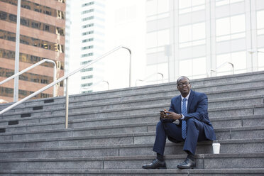 Businessman sitting on stairs with cell phone and takeaway coffee - WESTF22656