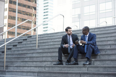 Two businessmen sitting on stairs talking - WESTF22659