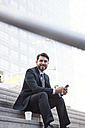 Smiling businessman sitting on stairs with cell phone and takeaway coffee - WESTF22662