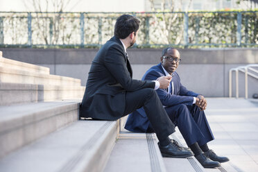 Two businessmen sitting on stairs talking - WESTF22665