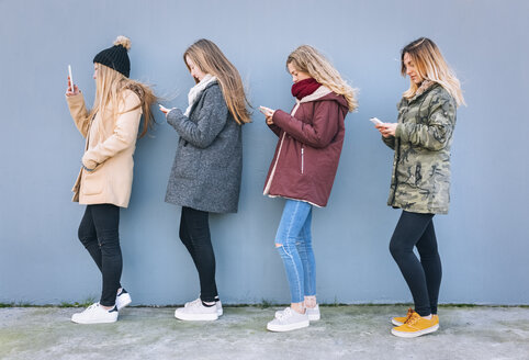 Four young women standing in a row using their cell phones - MGOF02922