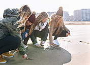 Four friends drawing in the sand on the beach - MGOF02925