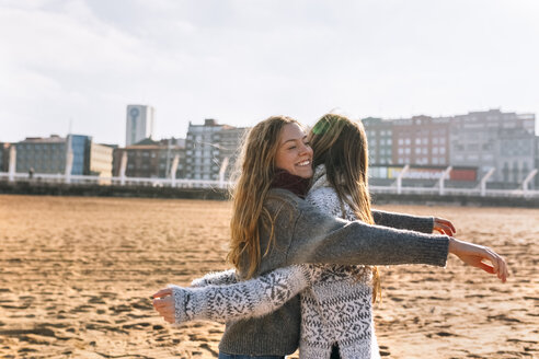 Two friends giving each other a hug on the beach - MGOF02937