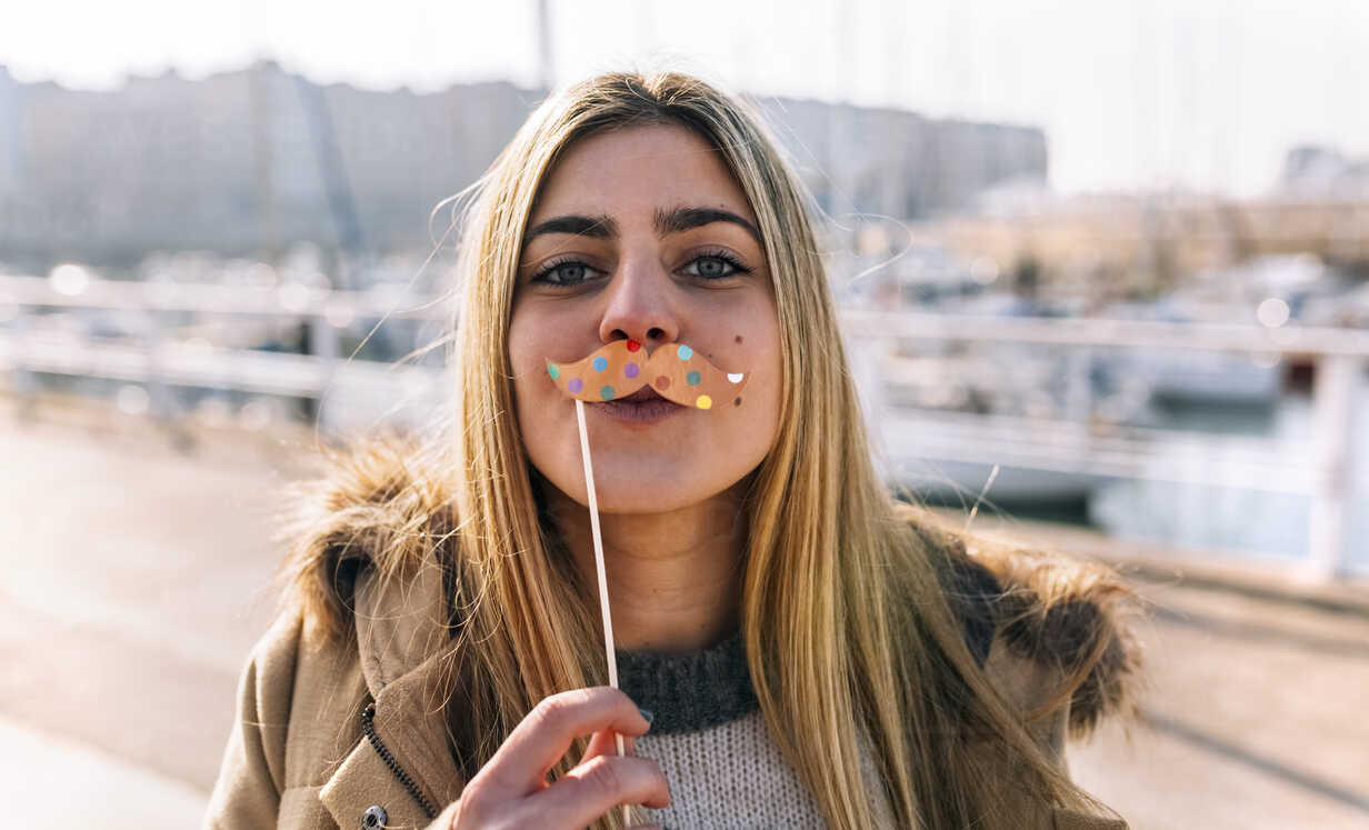 Portrait of teenage girl with toy moustache - MGOF02943 - Marco Govel/Westend61