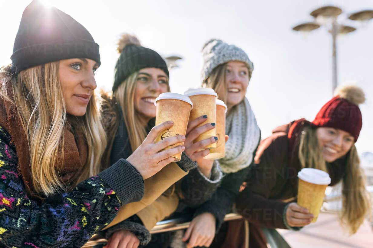 Four friends toasting with coffee to go in winter - MGOF02946 - Marco Govel/Westend61