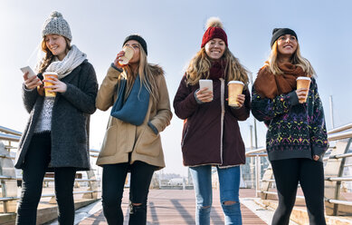 Four friends with coffee to go and cell phones walking on a bridge in winter - MGOF02949