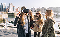 Teenage girl using wearing VR glasses while her friends watching her - MGOF02970