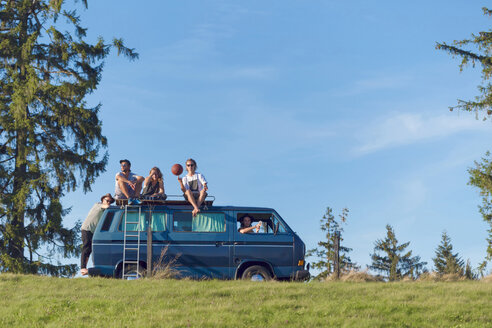 Group of friends sitting on van in the nature - WVF00838