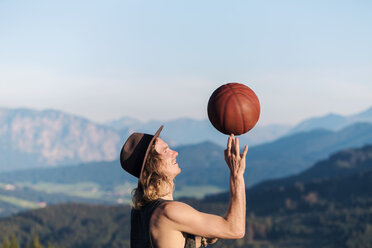 Austria, Mondsee, Mondseeberg, young man balancing basketball on his finger - WVF00844