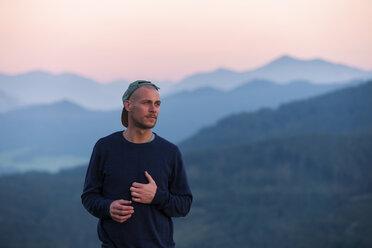 Austria, Mondsee, Mondseeberg, portrait of man wearing a basecap at dusk - WVF00847