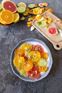 Plate of peeled and sliced citrus fruits with pistachios - SARF03180