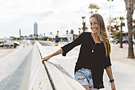 Portrait of happy young woman on waterfront promenade - GIOF01819