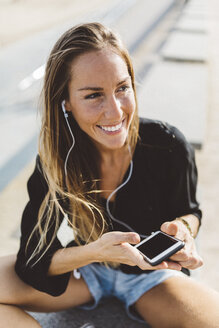 Happy young woman with cell phone and earbuds outdoors - GIOF01822