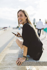 Happy young woman with cell phone and earbuds on waterfront promenade - GIOF01825