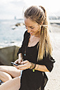Smiling young woman at the seafront using cell phone - GIOF01834
