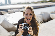 Portrait of happy young woman with old-fashioned camera at the seafront - GIOF01840