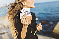 Young woman showing instant photos of herself at the seafront - GIOF01846