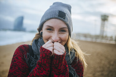 Portrait of smiling young woman on the beach in winter - KIJF01183