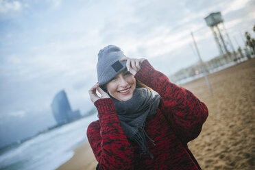 Portrait of smiling young woman on the beach in winter - KIJF01186