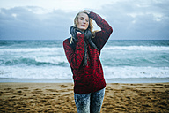Young woman with eyes closed on the beach in winter - KIJF01198